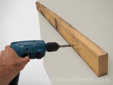 Mounting a 2 x 4 is the first step in how to install a fireplace mantel on your wall.