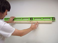 Use a level while holding the mounting strip on the wall.