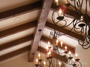 Faux wood beams paired with wrought iron chandeliers.
