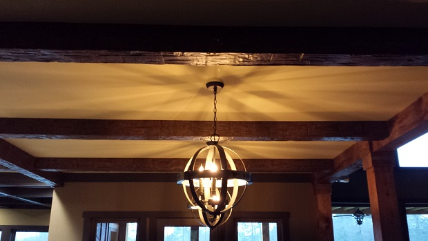 A home's large white ceiling is given more design character with real and faux beams.