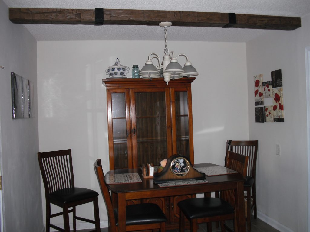 Dining room ceiling beam created with 3 leftover beam pieces with added straps to mimic the look of a single beam.
