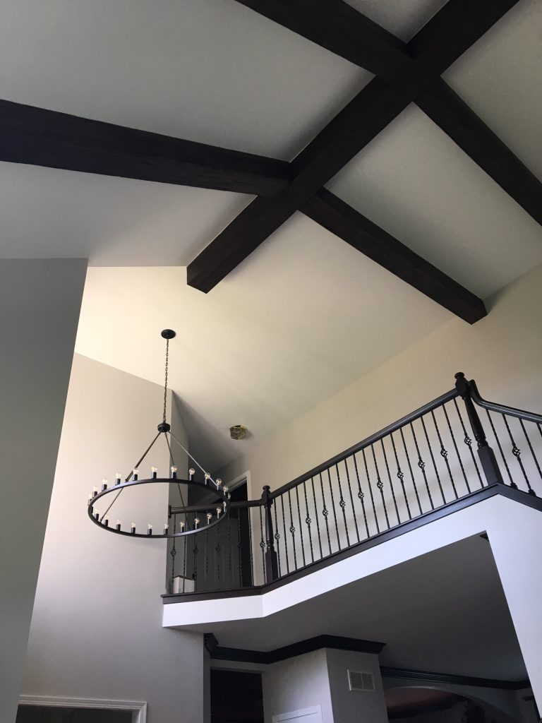 The beams look great alongside the medieval-style decor details, such as the wrought iron banisters and circle chandelier.