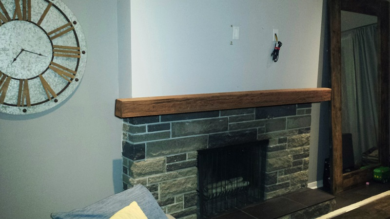 Custom Timber Mantel installed on a real stone fireplace.