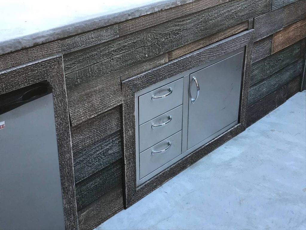 Drawers and cabinets on an outdoor kitchen framed with barn board style planks