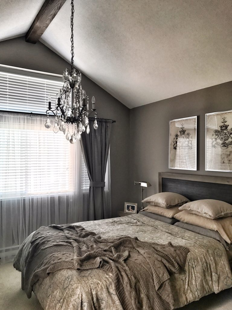 Remodeled bedroom with a beautiful chandelier installed through a Beachwood style faux beam.