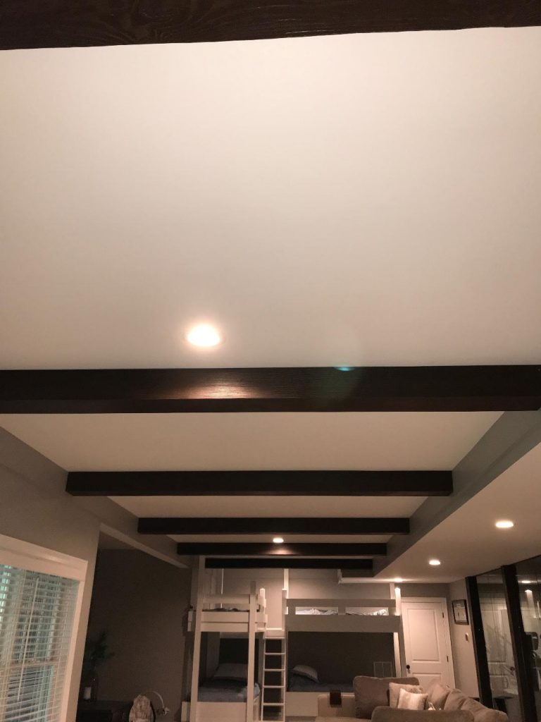 Woodland beams line the recessed ceiling of a home's finished basement.