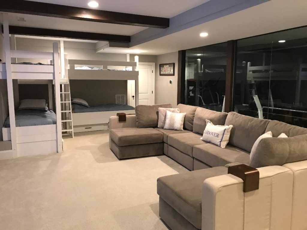 Finished basement designed with a home gym, large L-couch and bunk beds.
