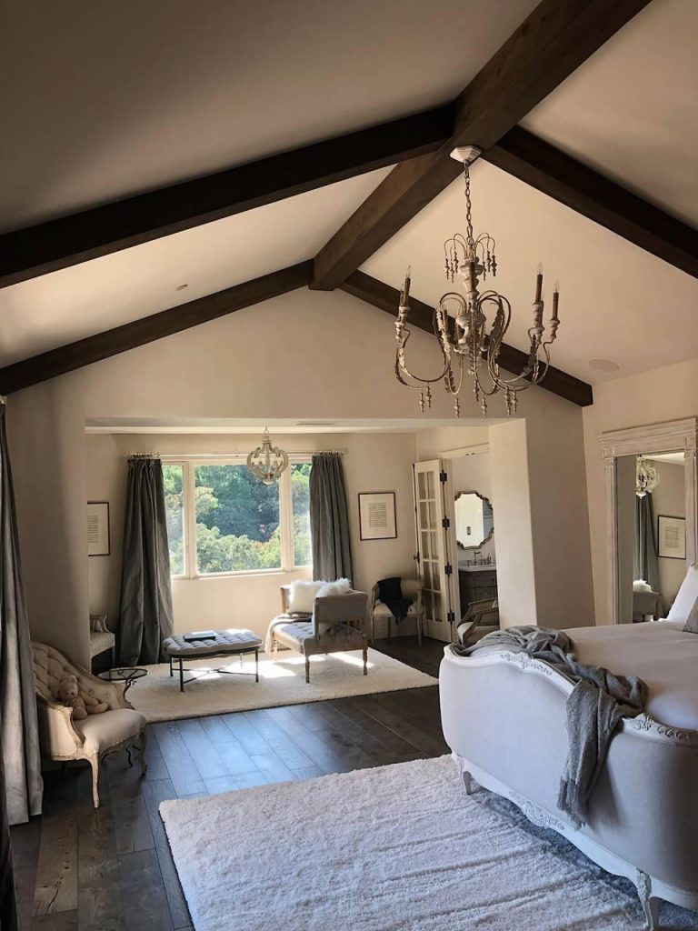 California home's bedroom with elegant furnishings, wrought iron chandelier and exposed decorative beams.