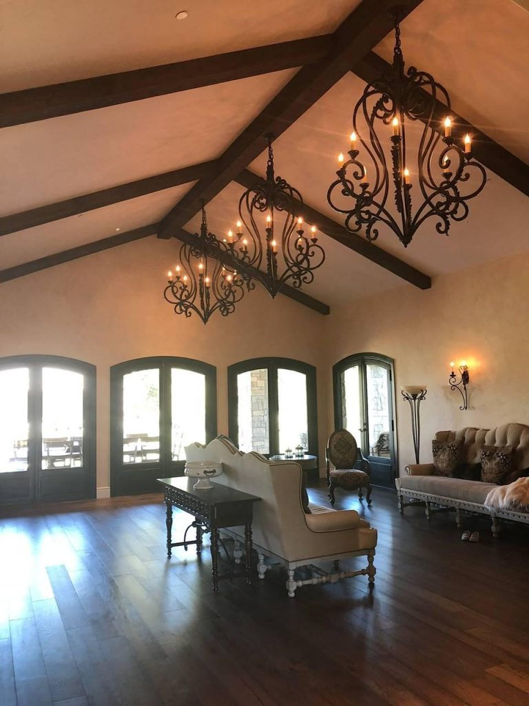 Elegant living room in Sonoma, CA with beams and wrought iron chandeliers