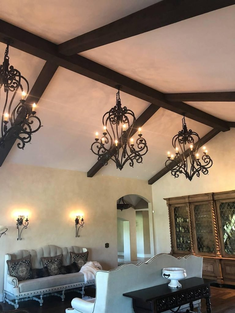 Elegant home design in Sonoma, CA featuring Barn Board and Wire Brushed box beams with wrought iron chandeliers in the living room.